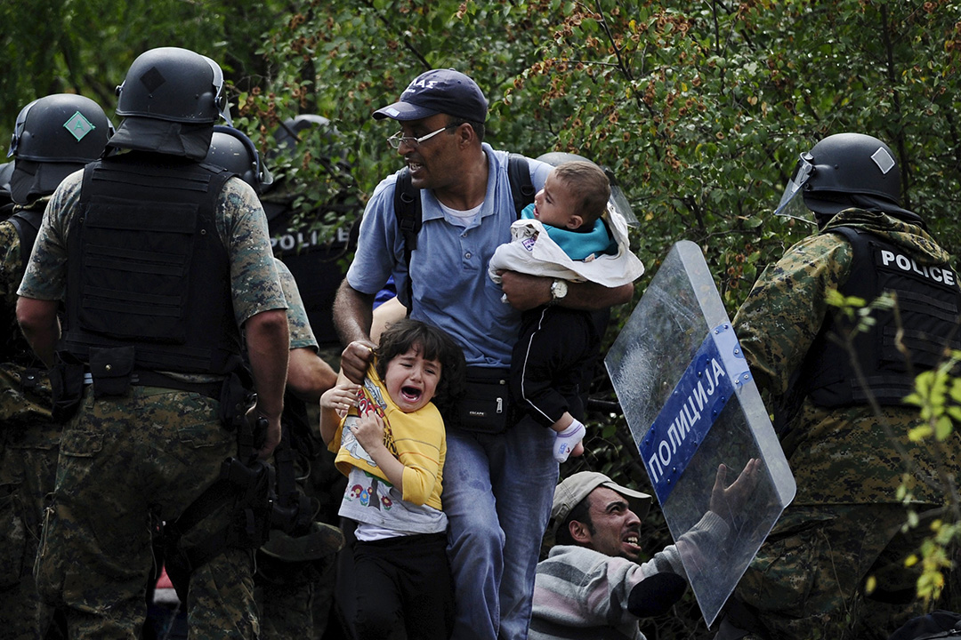 一名父親帶着兩名孩子越過希臘Macedonia邊境。八月中的一個星期六,數以百計難民同時取道Macedonia進入希臘,警方使用警棍和震撼彈驅趕難民,多人受傷。