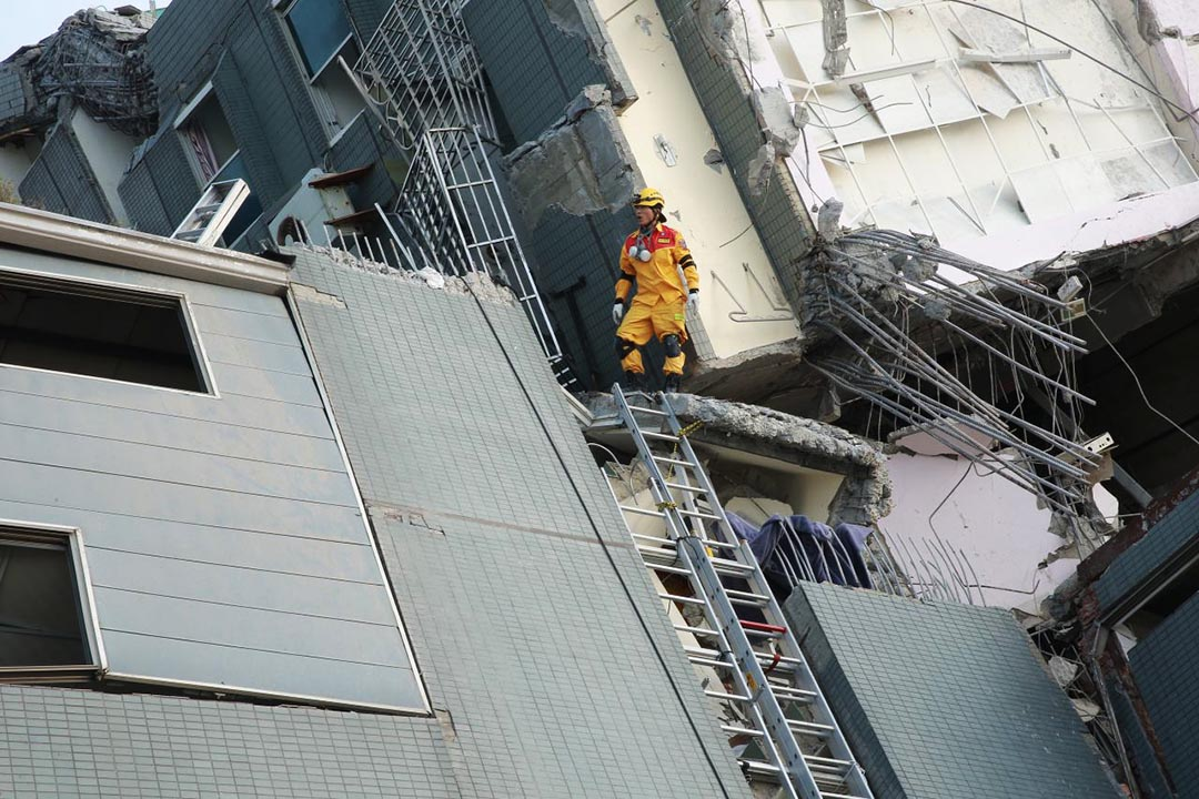 一名救援人員站在倒㙮危樓上視察。攝 : 徐翌全/端傳媒