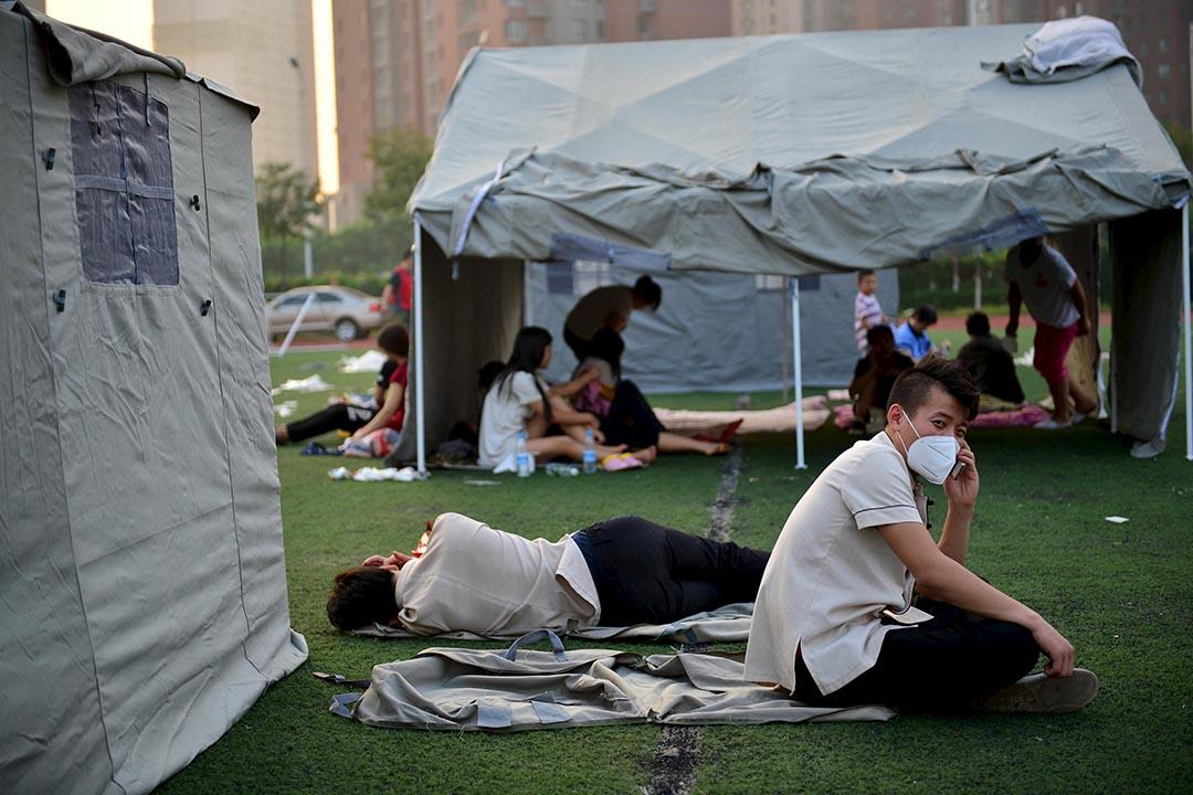 市民戴上口罩,在戶外帳篷休息。攝 : REUTERS