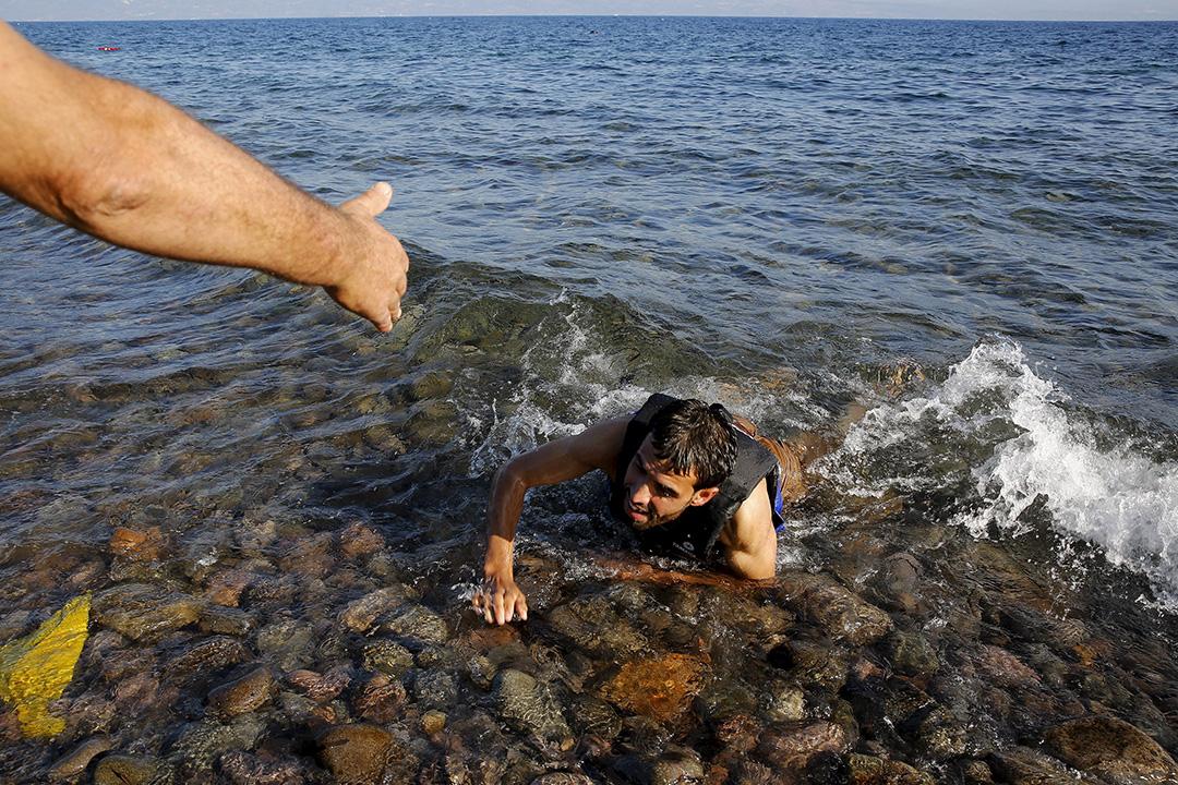 在希臘Lesbos島,一名本地人向敘利亞難民伸出援手。攝: Yannis Behrakis/ REUTERS