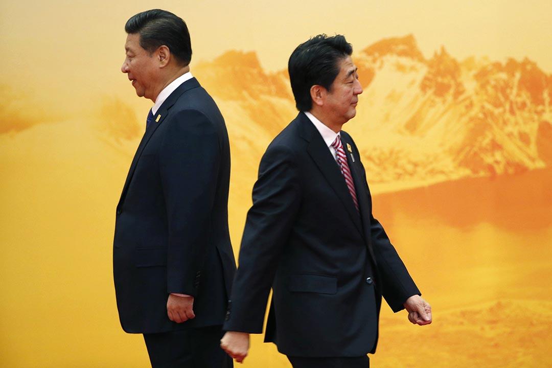 2014年11月的APEC會議上,日本首相安倍晉三在中國國家主席習近平身邊走過。攝: Kim Kyung-Hoon/REUTERS