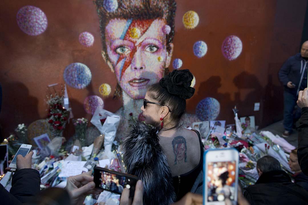 黃耀明認為,對於觀眾,David Bowie 的一生是那麼富有挑戰性,爭議中帶給大眾更多領會。圖為一名女性展示背部 David Bowie 紋身。攝:Matt Dunham/AP