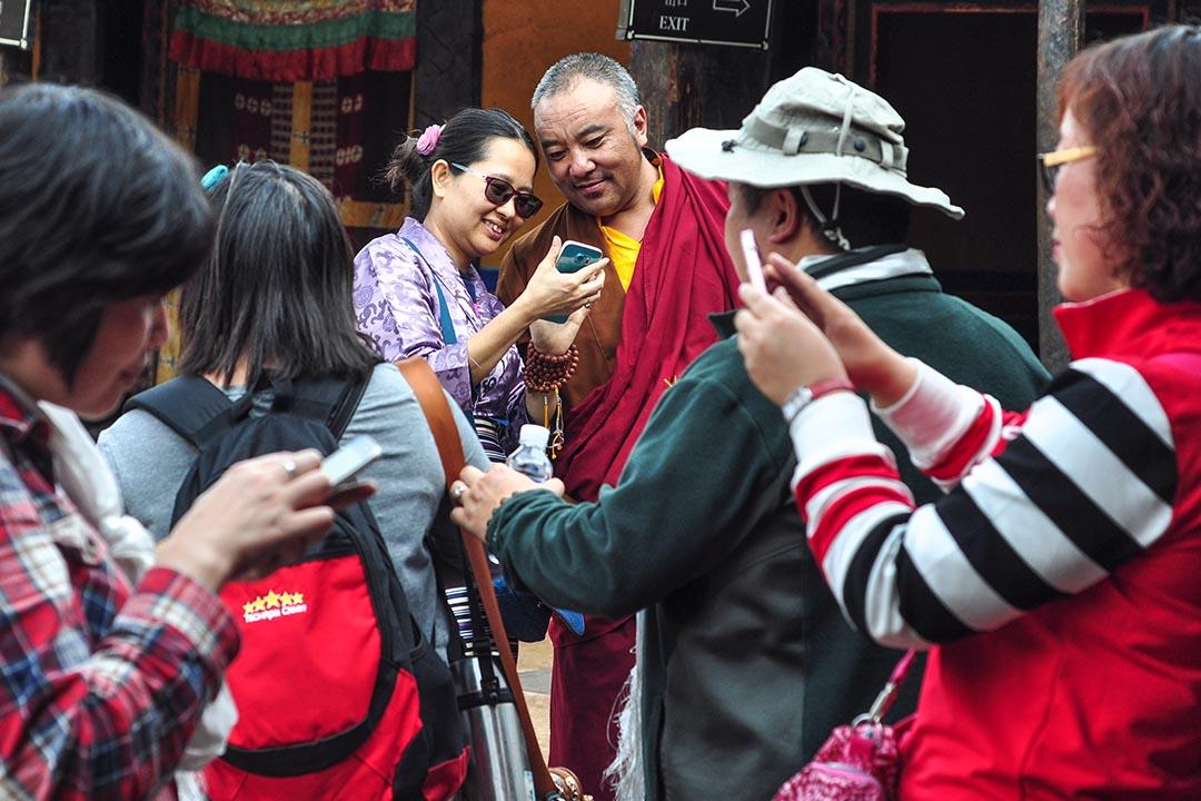 在拉薩大昭寺,內地遊客捉著一位僧人,逐一與他合照留念。問及僧人是誰,遊客表示不知道,只是見所有人都在拍,也就湊熱鬧一起拍。攝 : Pazu Kong/端傳媒