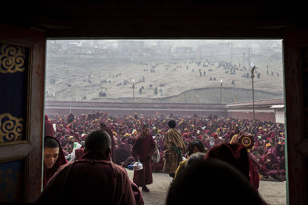 在色達喇榮五明佛學院內,一些喇嘛在喝茶,背後坐著成千的喇嘛。攝:Kevin Frayer/Getty Images