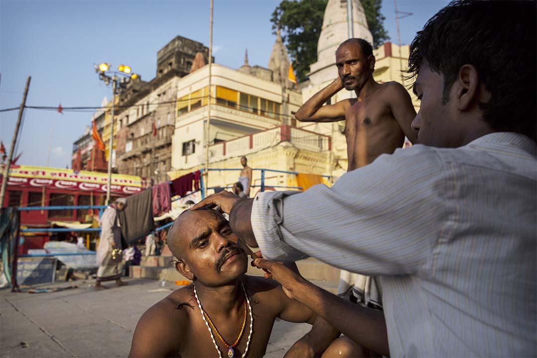 瓦拉納西的街道上一名男人在剃頭。攝:Kevin Frayer/Getty