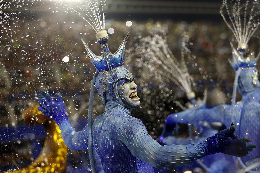 在巴西里約熱內盧,一群舞者在表演,頭上噴出水柱。攝:Silvia Izquierdo/AP Photo