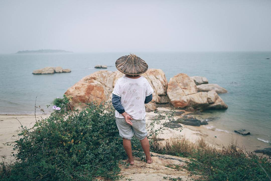 村民在海邊遠眺小嶝島。攝:王嘉豪/端傳媒