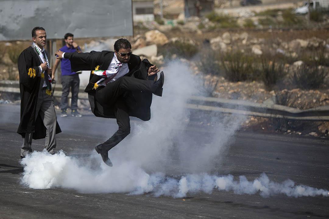 2015年10月12日,巴勒斯坦拉姆安拉,  一名律師在律師公會發起的遊行中腳踢催淚彈罐。攝:Majdi Mohammed/AP