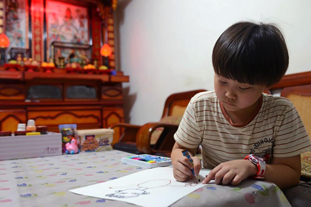 2013年台北,一名七歲男生在家中做功課。攝:Sam Yeh/AFP