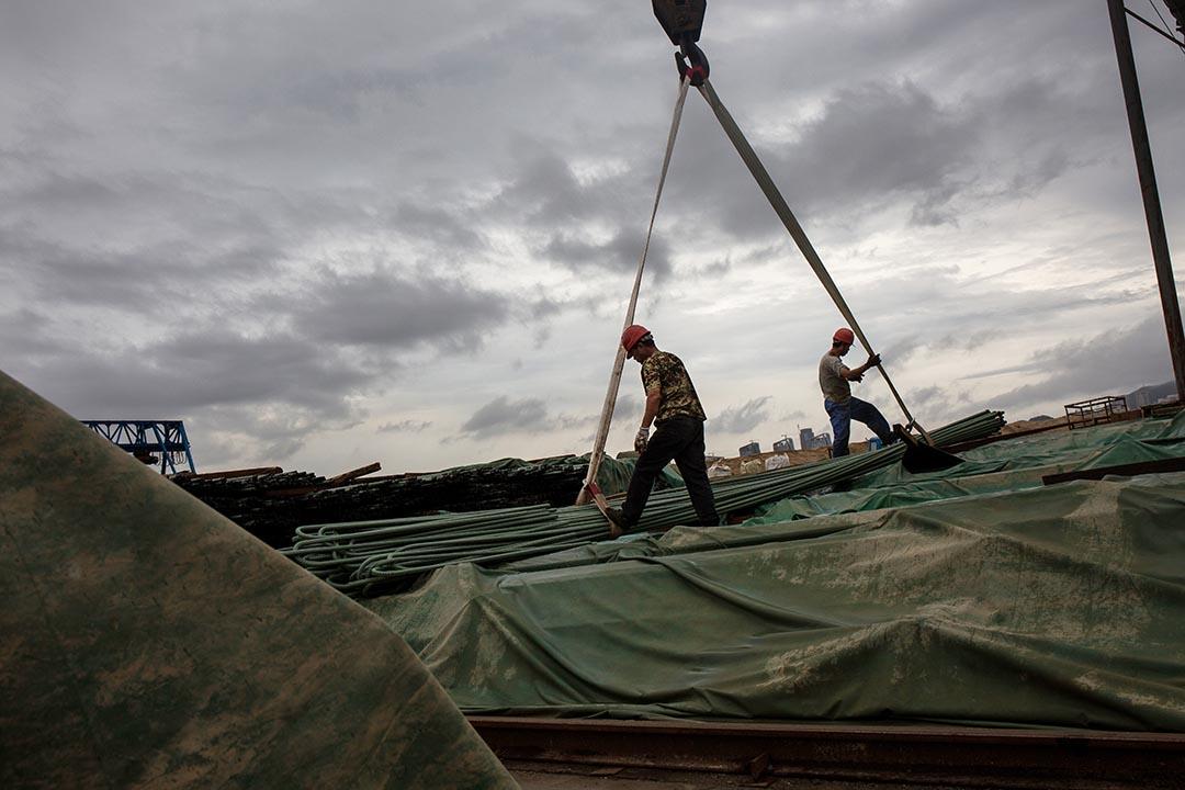 工人用起重機吊起建橋用的鋼支 。