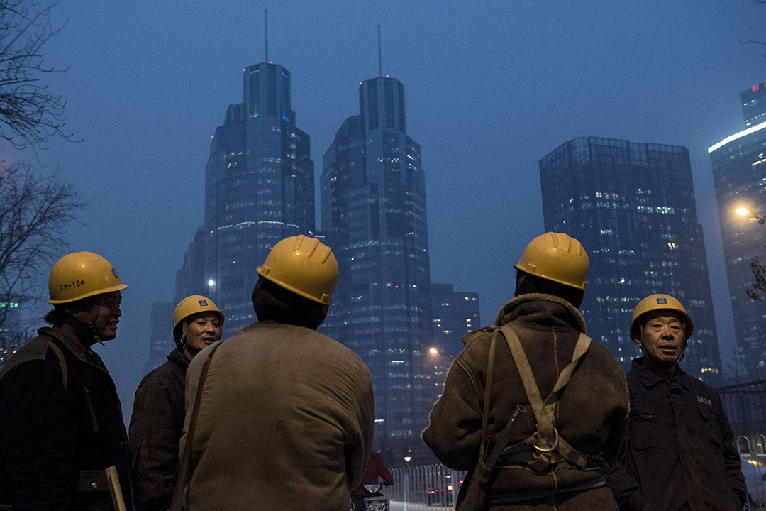 2015年12月9日,北京,工人下班後在地盤附近閒聊。攝:Kevin Frayer/GETTY