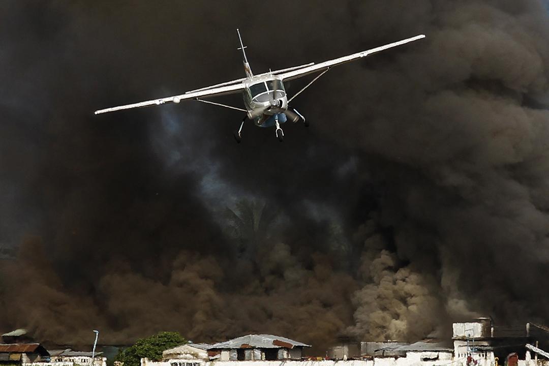 Kalay市的油站冒出大量黑煙,飛機接走部分災民。攝: Soe Zeya Tun /REUTERS