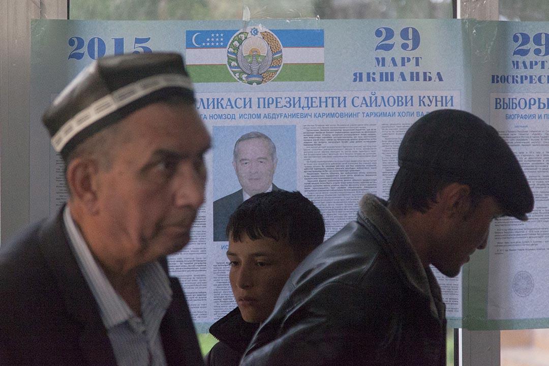 幾名男子在烏茲別克斯坦總統選舉海報前走過。REUTERS