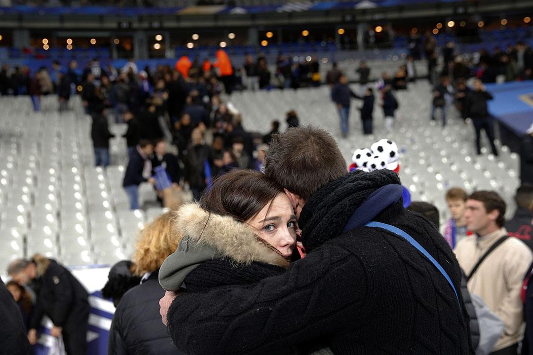 球場受襲後,兩名觀眾相擁互相安慰。攝:Christophe Ena/AP