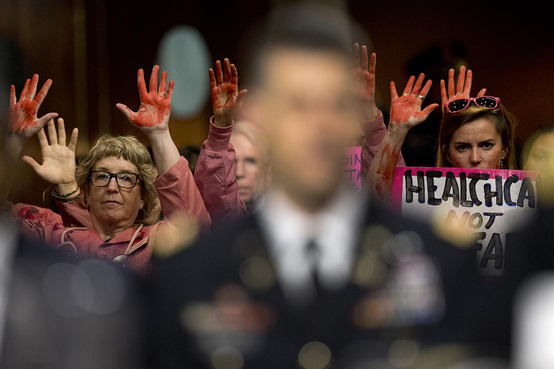 民眾在美國參議院軍事委員會(Senate Armed Services Committee)的聽證會上抗議美軍轟炸阿富汗醫院。攝:Carolyn Kaster/AP