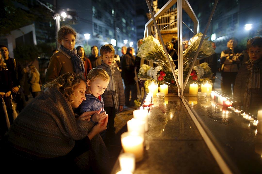 2015年11月14日,韓國首爾一名母親與孩子點起蠟燭悼念巴黎恐怖襲擊的遇難者。攝:Kim Hong-Ji/REUTERS