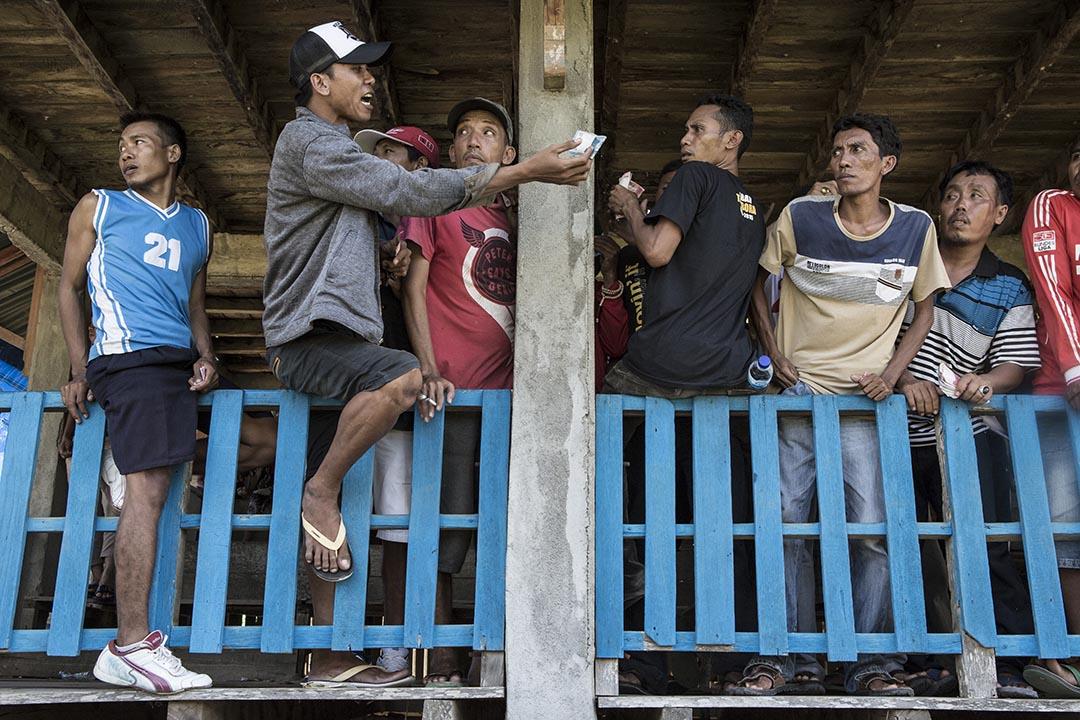 手持印尼盾的觀眾在場邊落注。攝:Putu Sayoga