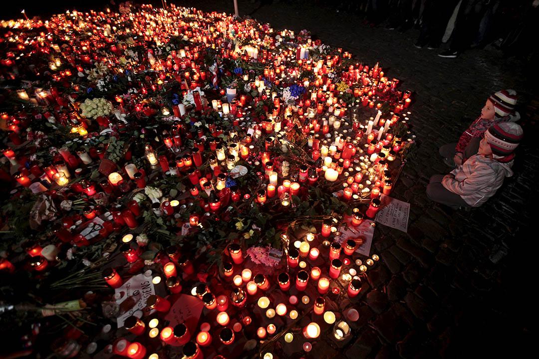 2015年11月14日,捷克布拉格的法國領事館外放滿了鮮花和蠟燭以示哀悼,兩名小孩在燭光前祈禱。攝:David W Cerny/REUTERS