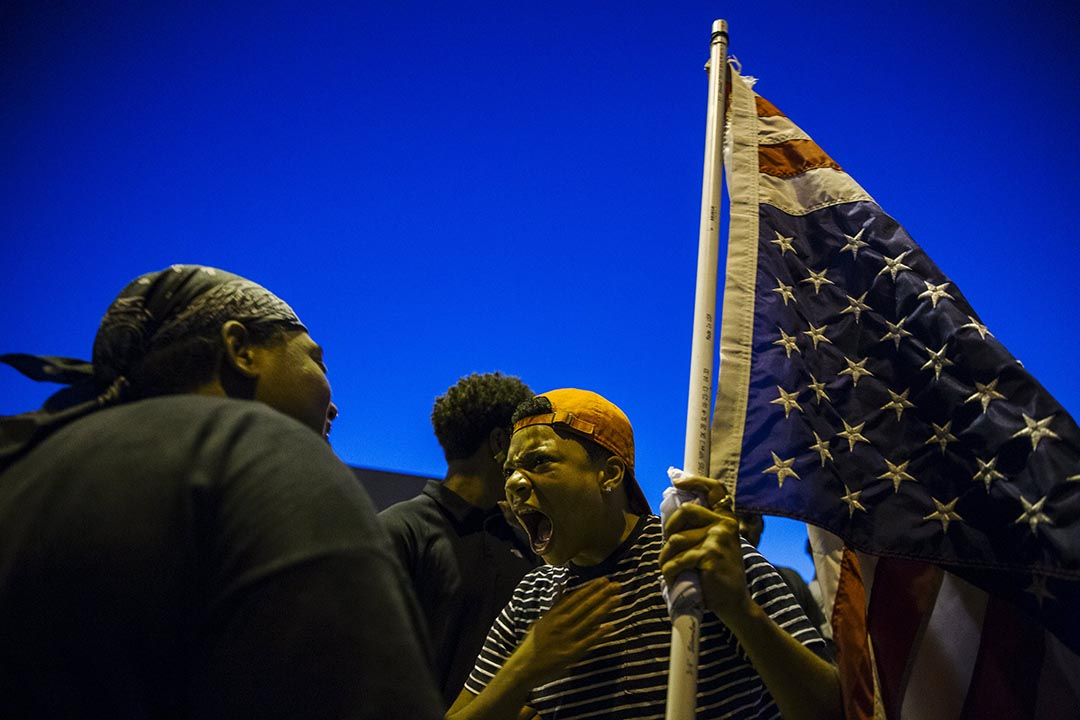 紀念黑人青年布朗(Michael Brown)被槍殺一週年遊行中,一個手持倒掛美國國旗的示威者吶喊示抗議。攝 : Lucas Jackson/REUTERS