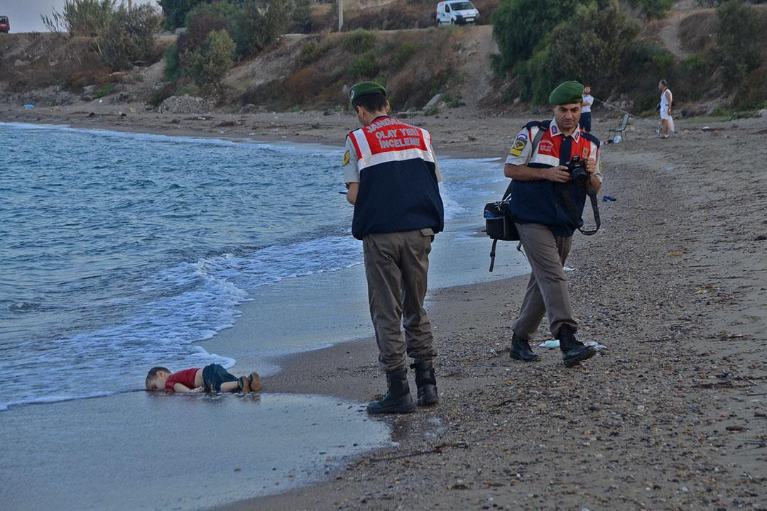 土耳其憲兵在一名溺斃的三歲小童Aylan Kurdi屍體旁調查,Aylan Kurdi一家四口登上偷渡船隻希望前往歐洲生活,不幸在土耳其對出海洋沉沒。Aylan Kurdi和哥哥及母親一同溺斃,當父親前往認屍後向傳媒表示,家人死去令他打消前往歐洲的念頭,準備返回敘利亞。