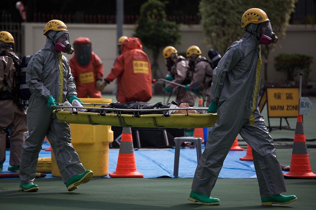 兩名穿著 C 級化學保護袍消防人員模擬運送傷者離開。攝:盧翊銘/端傳媒
