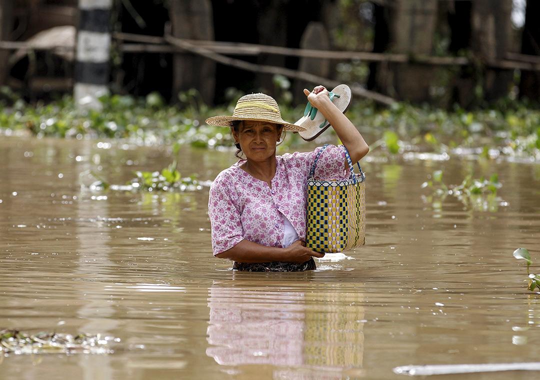 一名女士在災區中涉水行走。摄: Soe Zeya Tun /REUTERS