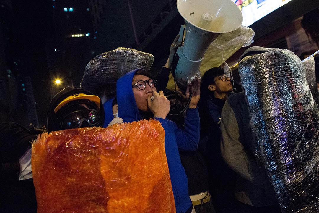 2016年2月9日凌晨,旺角,梁天琦(藍色衣服)和其他示威者在旺角與防暴警發生衝突。攝:盧翊銘/端傳媒