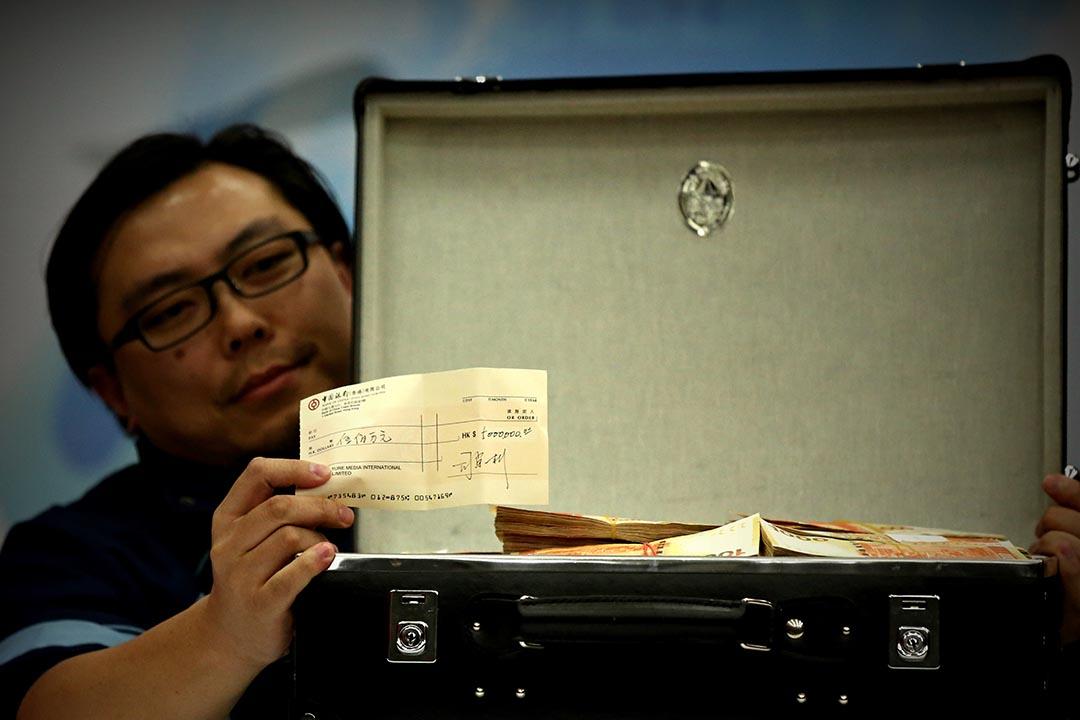 3月4日,亞視投資者一方中午在亞視大埔廠房召開記者會,期間展示一箱500萬元現金及一張500萬元支票。攝:盧翊銘/端傳媒