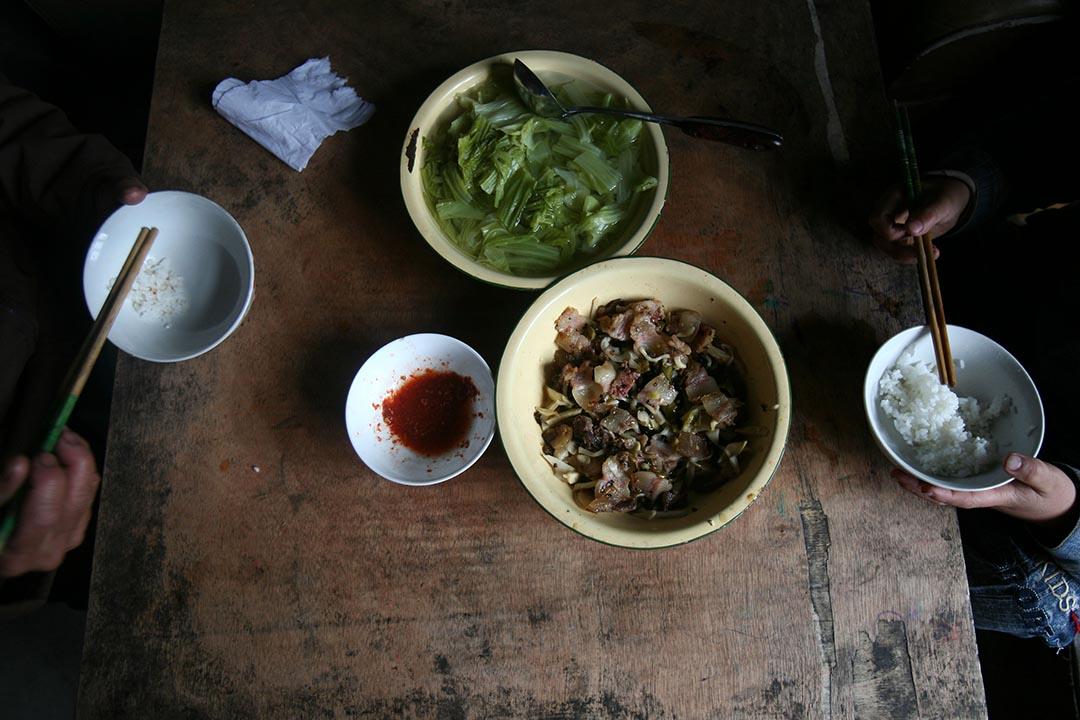 15歲和12歲的兩姐弟在中國貴州省畢節市納雍縣勺窩鄉中心村的家裏被發現死亡。圖為兩名留守兒童在祖母家吃午餐。攝 : Stringer/Getty Images