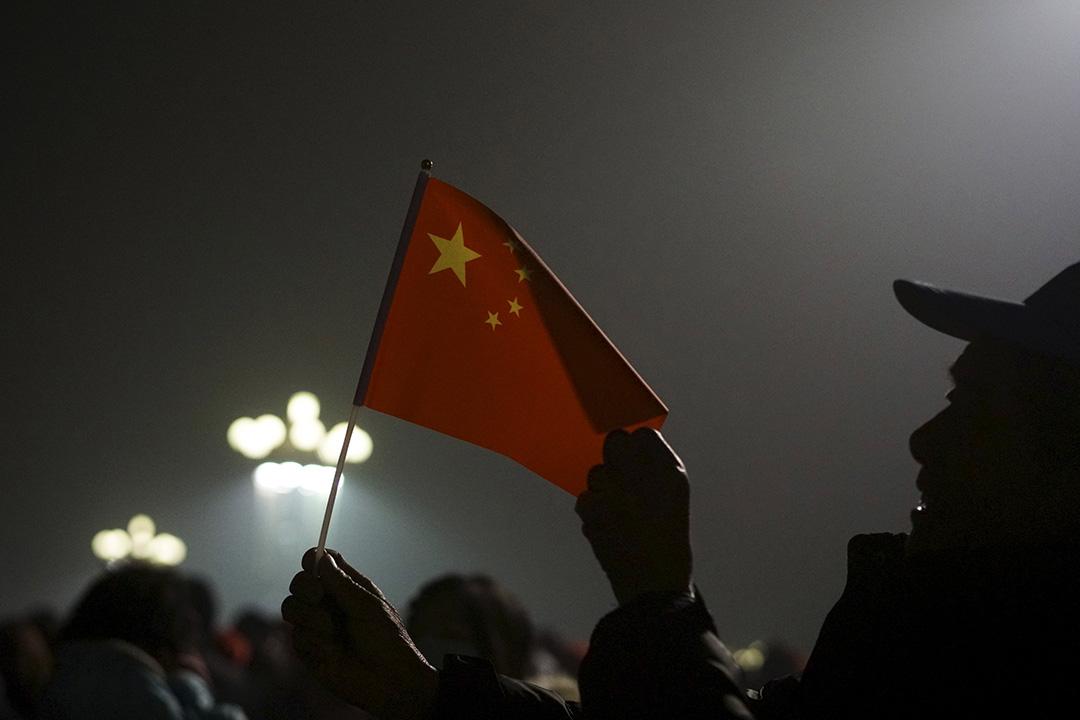 2015年12月1日,北京,手持國旗的市民在天安門廣場等候觀看升旗禮。攝:Stringer/REUTERS