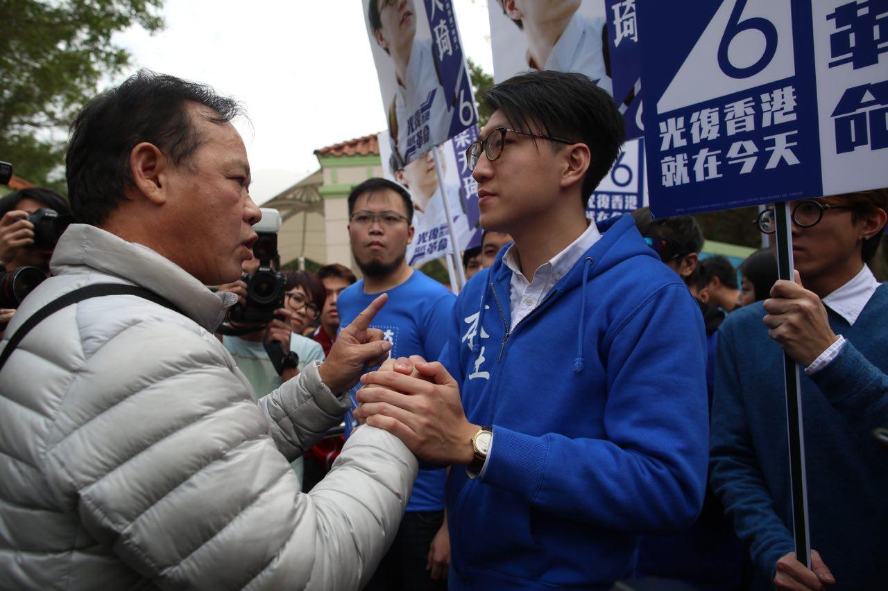 建築公司老闆陳先生(左)在上水與本民前候選人梁天琦握手,表達對梁的支持。 攝:羅國輝/端傳媒