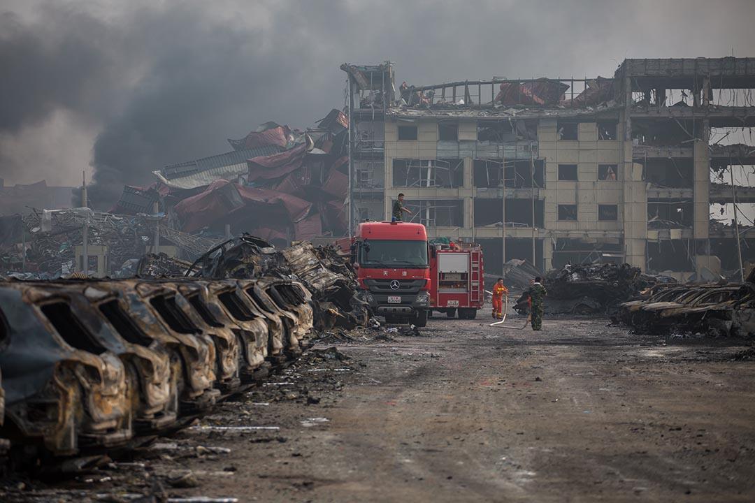 2015年8月14日,天津,消防員在爆炸現場的房車殘骸旁邊戒備。攝: Billy H.C. Kwok/ 端傳媒