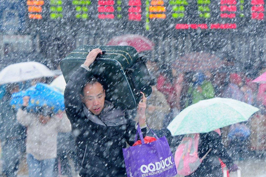 2016年1月31日,江西省一個火車站,一名男子大雪中抬著行李走過。攝:China Daily/REUTERS