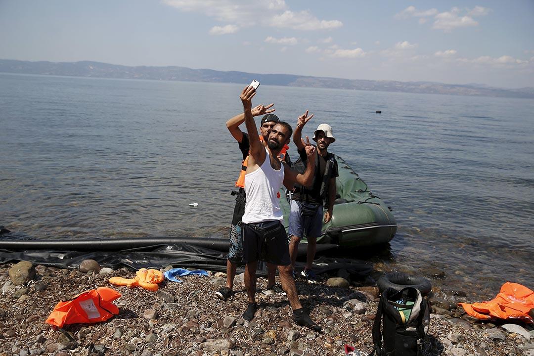 2015年8月23日,希臘。來自敘利亞的難民登岸後用手機自拍。攝:Alkis Konstantinidis /Reuters