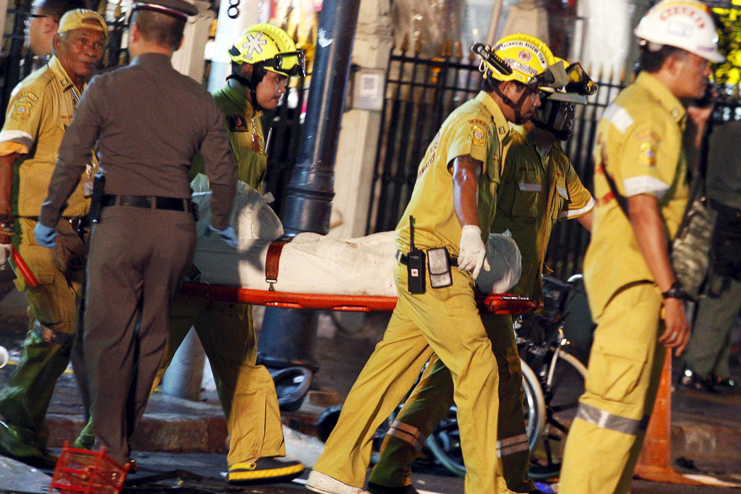 消防員抬走被白布包裹的遺體。
