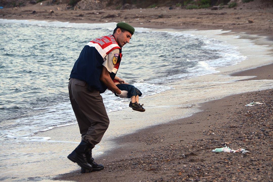 一名土耳其警員抱走3歲難民男孩的屍體,男孩伏屍海灘的照片在網絡瘋傳,為難民危機敲響人道主義警鐘。攝 : Nilufer Demir/DHA/REUTERS