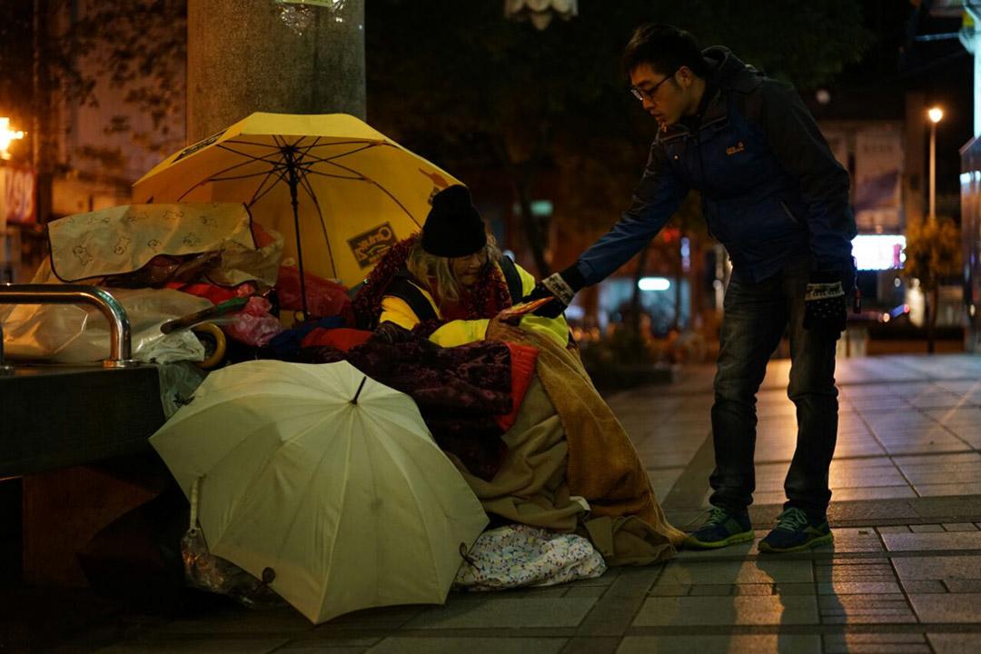2016年1月24日,台北龍山寺,志工向街友派發物資及暖包。攝:張國耀/端傳媒