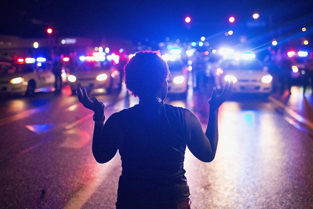 美國密蘇里州弗格森市進行紀念黑人青年布朗(Michael Brown)被槍殺一週年活動,一名示威者舉起雙手面向警察。攝 : Scott Olson/GETTY