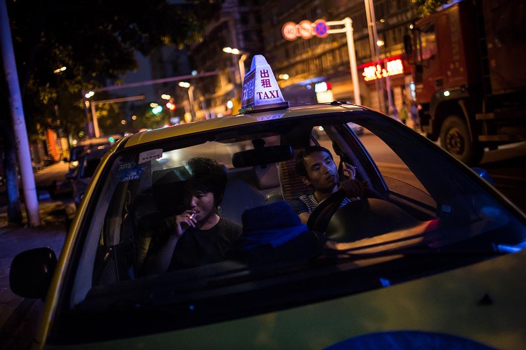 2015年8月11日,重慶,劉偉偉(左)在出租車上與司機聊天。攝: Billy H.C. Kwok/ 端傳媒