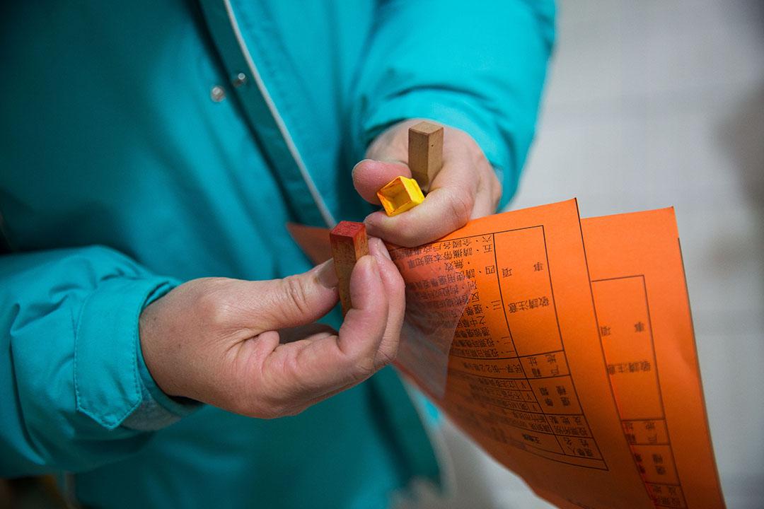 投票當天,謝素嬉拿著印章與通知單到投票站。攝:Billy H.C. Kwok/端傳媒