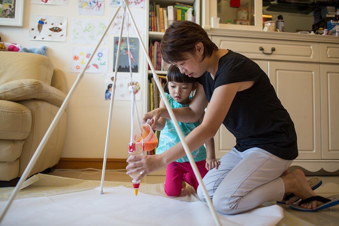 7 . 鋪上膠地墊和畫紙,架上支架,緊記要先把唧嘴關閉,才將顏料注入膠樽,然後讓小孩擺動膠樽,看顏料慢慢滴漏在畫紙上。