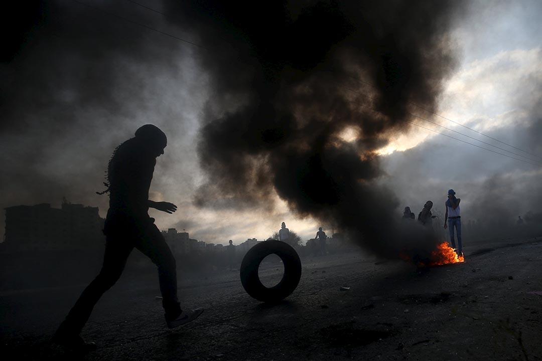 2015年10月5日約旦河西岸, 一名巴勒斯坦示威者滾動輪胎作為障礙物。 攝:Mohamad Torokman/REUTERS