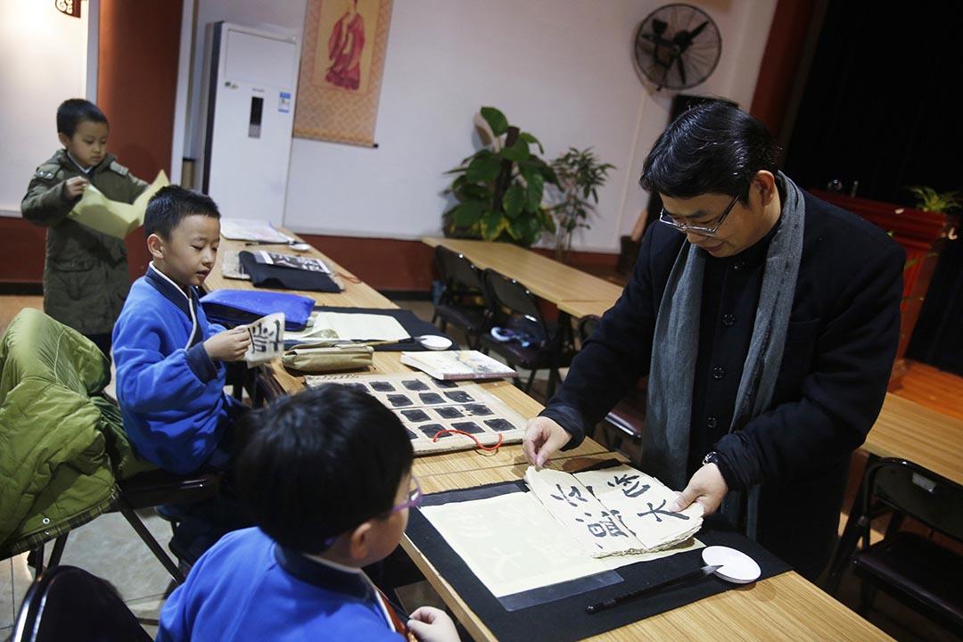 北京四海孔子書院的創辦人馮哲在論語堂看望正在練習書法的學生。攝:Wu Hao/端傳媒