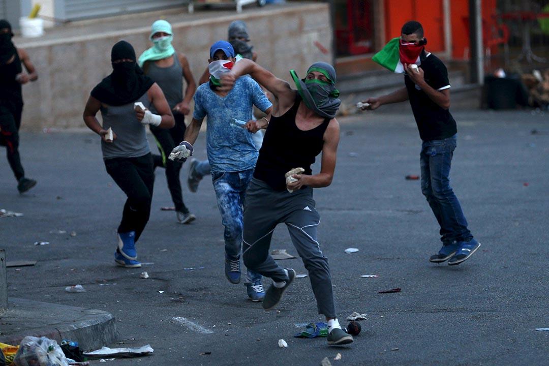2015年9月30日,約旦河西岸,巴勒斯坦示威者向以色列保安部隊投擲雜物。攝:Mohamad Torokman/REUTERS