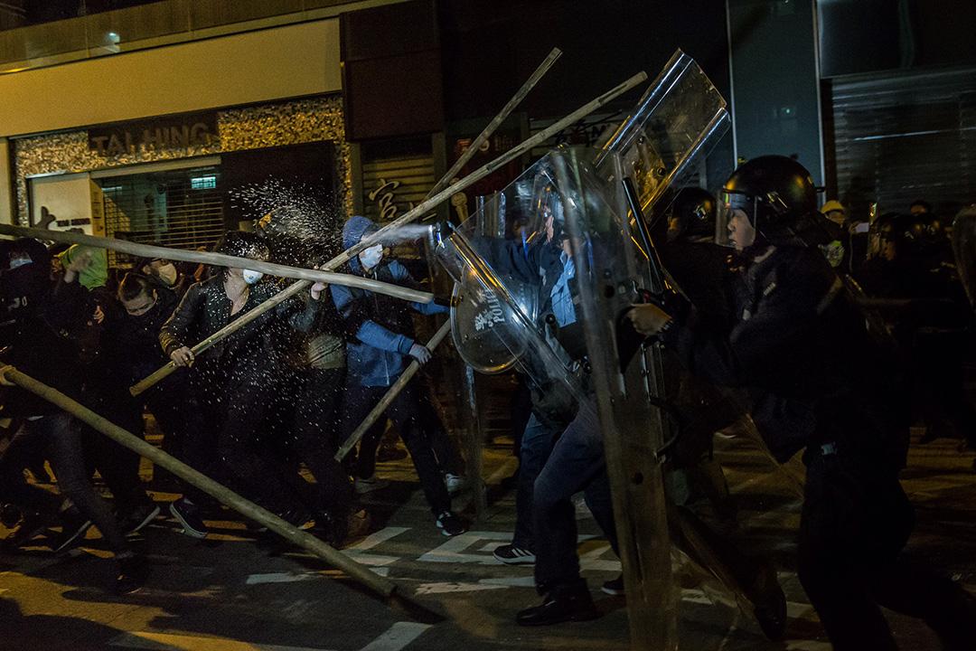 2016年2月9日,旺角,早上4時許,示威者以竹枝抵擋防暴警察,警方施放胡椒噴霧。攝:Billy H.C. Kwok/端傳媒
