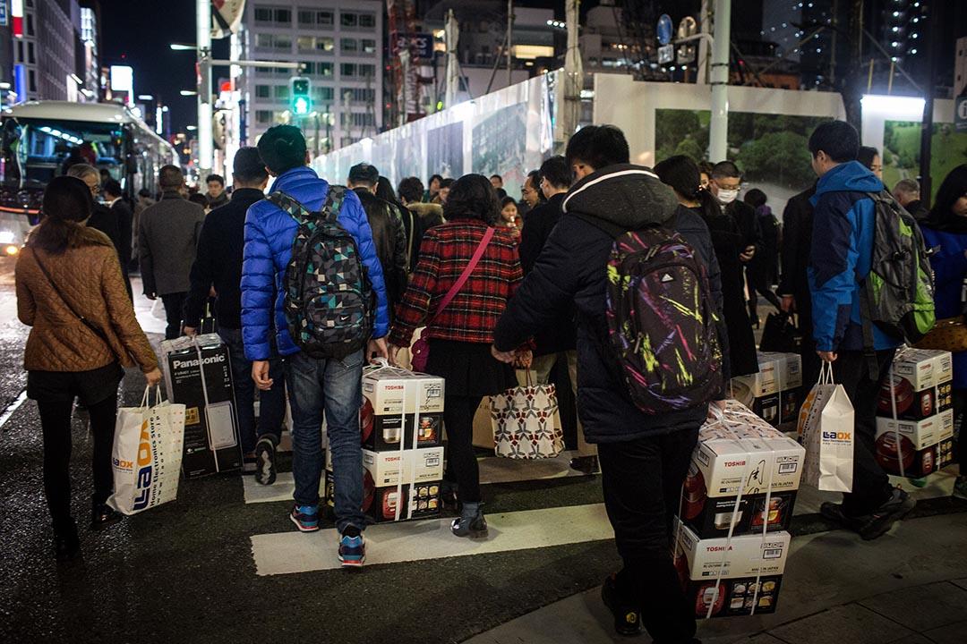遊客攜帶剛購買的商品橫過馬路。攝 : Chris Mcgrath/GETTY
