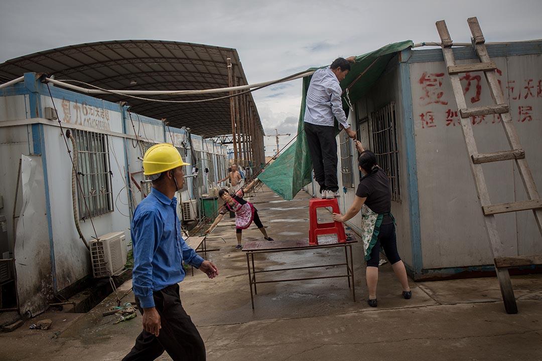 人工島的臨時宿舍由貨櫃一排排並列組裝而成,夏季颱風暴雨特別頻繁,設於戶外的臨時宿舍尤其受到影響,工人們正在加設帆布帳篷。