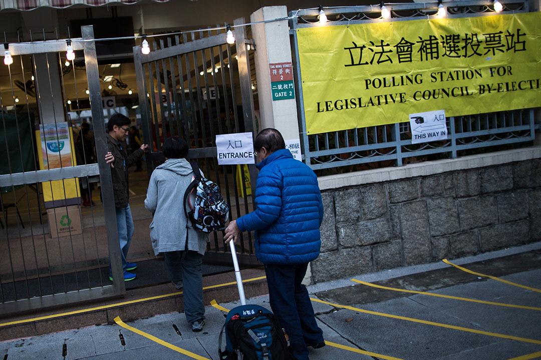 沙田第一城呂明才小學票站的職員在今晨7時半開始投票一刻打開閘門,讓選民進入票站投票。  攝:盧翊銘/端傳媒