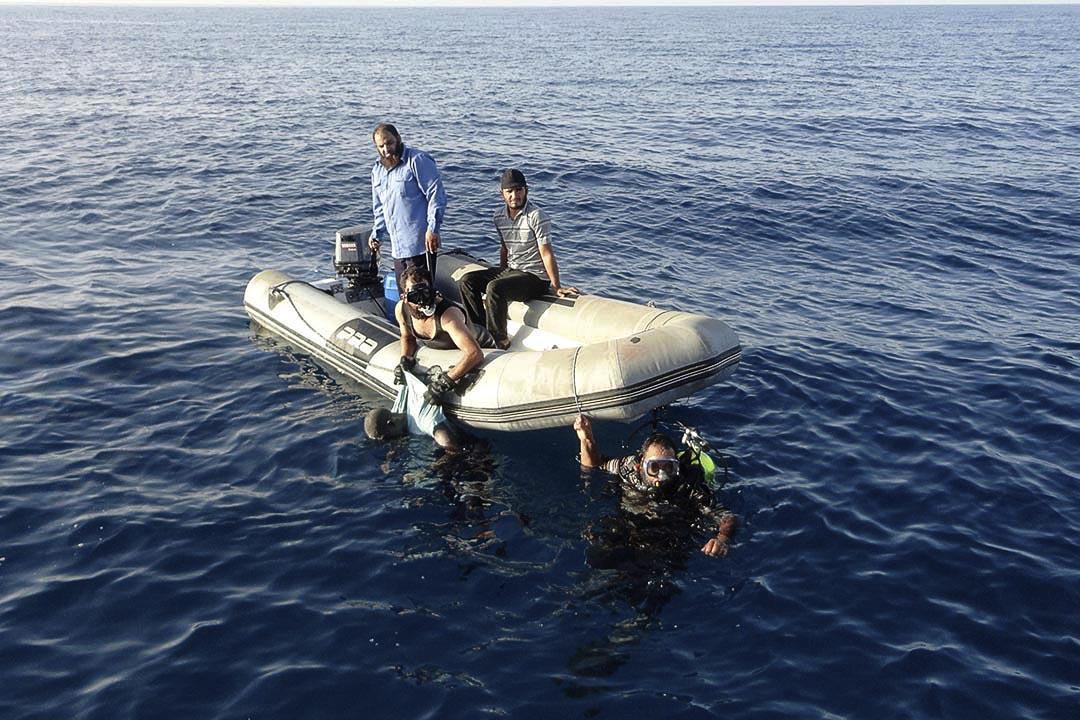 7月22日,一艘偷渡小船在利比亞外海沉沒。圖為利比亞海岸成員於海裡打撈在黎波里海岸溺斃的難民屍體。攝: Aimen Elsahli/REUTERS