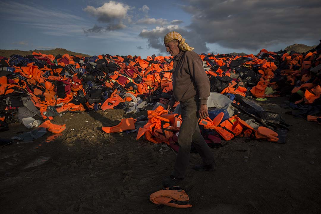 2015年12月2日,希臘萊斯沃斯島,一名男子在一堆難民登島後棄置的救身衣前走過。攝:Santi Palacios/AP